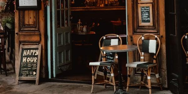 Außenbereich eines Gastronomiebetriebs mit Tischen, Stühlen und einer Tafel mit Happy Hour