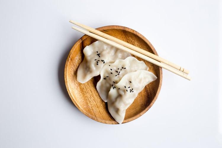 Dumplings serviert auf einem Bambusteller mit Essstäbchen