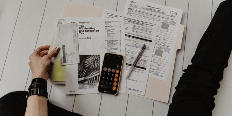 Rechner und Rechnungspapiere auf dem Boden