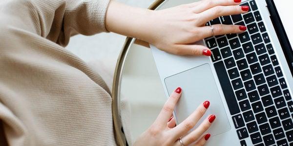 Frau schreibt einen Beitrag für google business an ihrem Laptop
