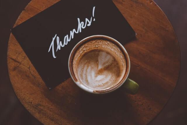 """Eine Karte mit """"Thanks"""" und eine Tasse Kaffee auf einem kleinen Bistro-Tisch"""