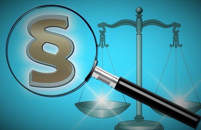 Rechtlicher Hintergrund - Lupe mit Paragraphensymbol in blau