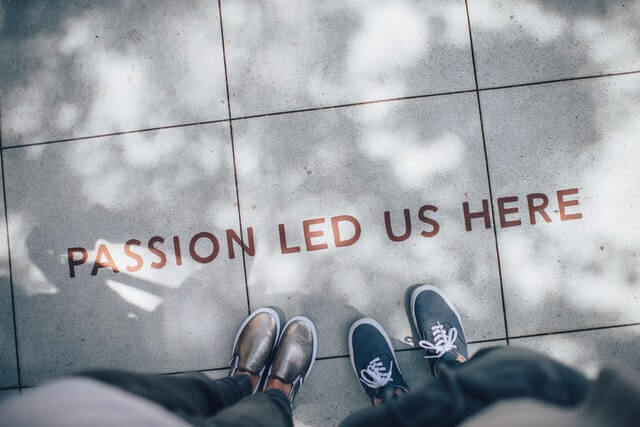 Schriftzug Passion led us here auf dem grauen Asphaltboden mit Schuhen
