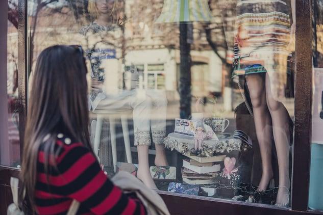 Frau überlegt Kleidung zu kaufen